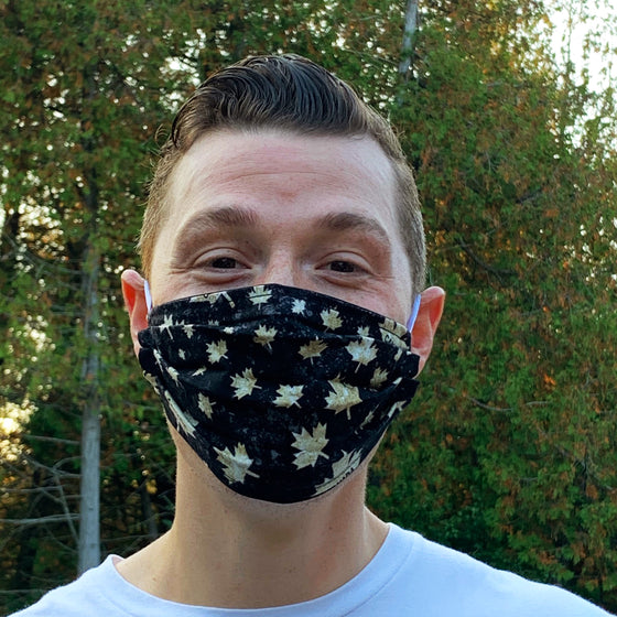 "A male model wearing a black face mask featuring cream coloured maple leaves and ""Canada."" Two elastic ear bands are included for easy wearability."