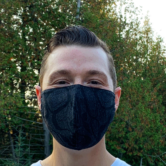 A male model wearing a black and grey mask with partial design of a Nuxalt style eagle. Two adjustable elastic earbands are included for easy wearability.
