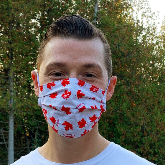 "A male model wearing a white face mask featuring red maple leaves and the words ""Canada"" and ""Eh"". Two elastic earbands are included for easy wearability."