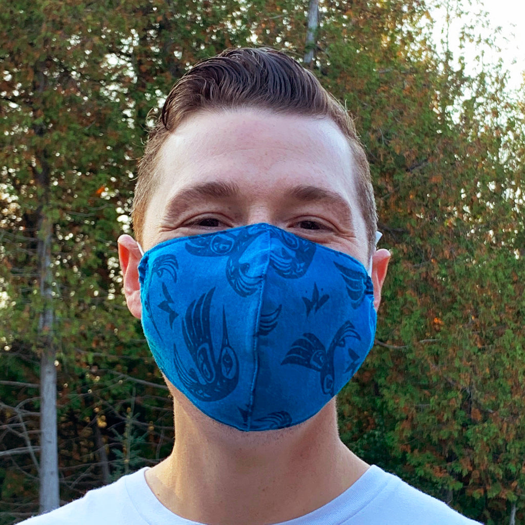 A male model wearing a blue face mask with a repeating image of a Nuxalt style hummingbird. Two adjustable elastic earbands are included for easy wearability.