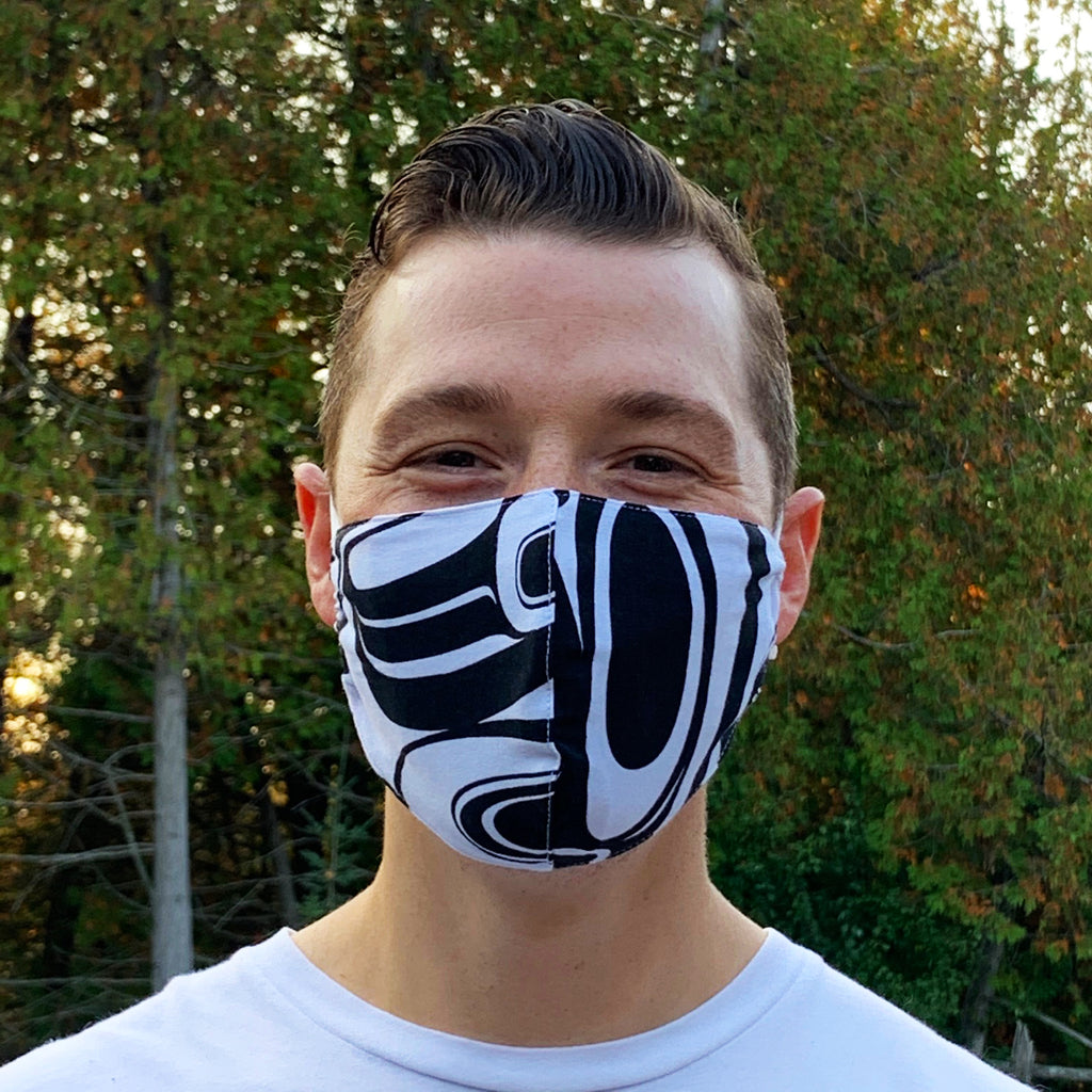 A male model wearing a black and white face mask with a partial design of a Nuxalt style raven. Two adjustable elastic earbands are included for easy wearability.