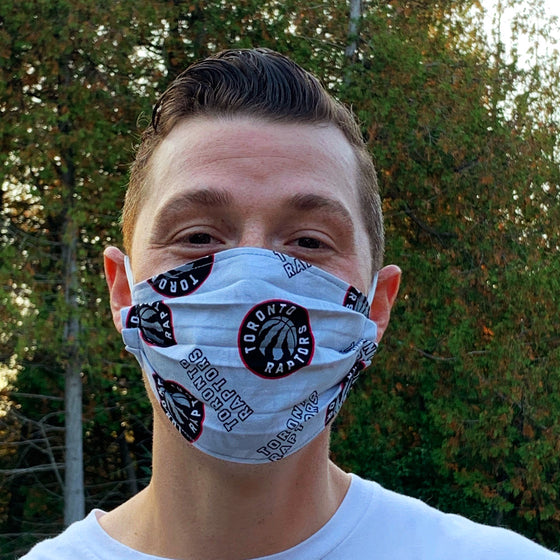 A male model wearing a grey face mask with a repeating pattern of the Toronto Raptors logo. Two elastic earbands are included for easy wearability.