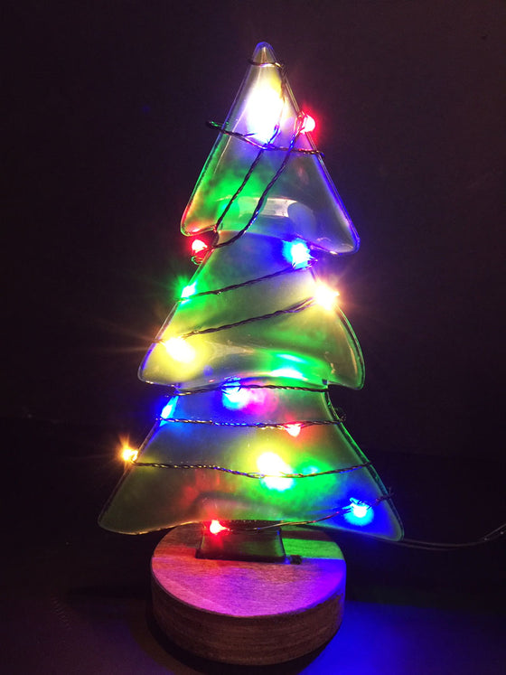 A pine tree made from green semi-transparent glass stands on a circular wooden base. A wire with multi-coloured lights is wrapped around the tree, lighting the tree up beautifully.
