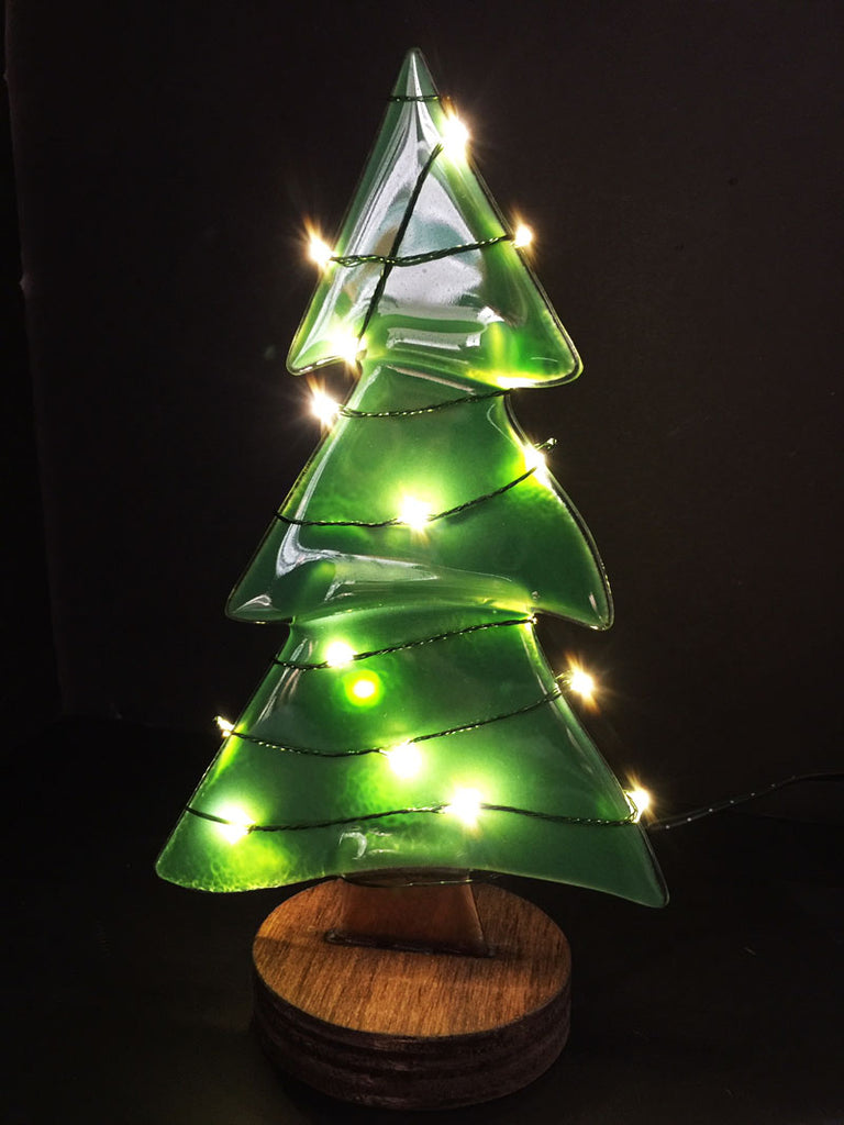 A pine tree made from green semi-transparent glass stands on a circular wooden base. A wire with white lights is wrapped around the tree, lighting the tree up beautifully.