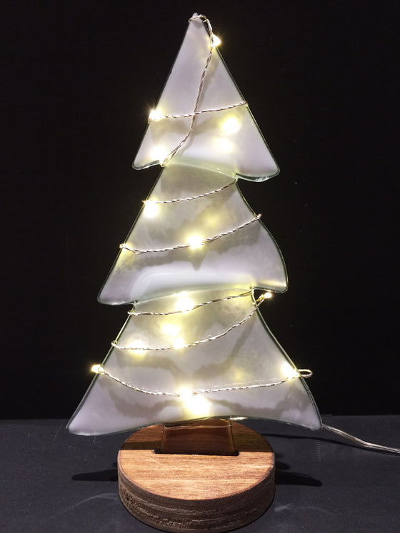 A pine tree made from white semi-transparent glass stands on a circular wooden base. A wire with white lights is wrapped around the tree, lighting the tree up beautifully.