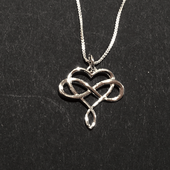 A sterling silver infinity symbol intertwined with a heart hangs from a silver chain. The infinity symbol crosses the middle of the heart horizontally. The bottom of the heart twists to form a loop reminiscent of the infinity symbol.
