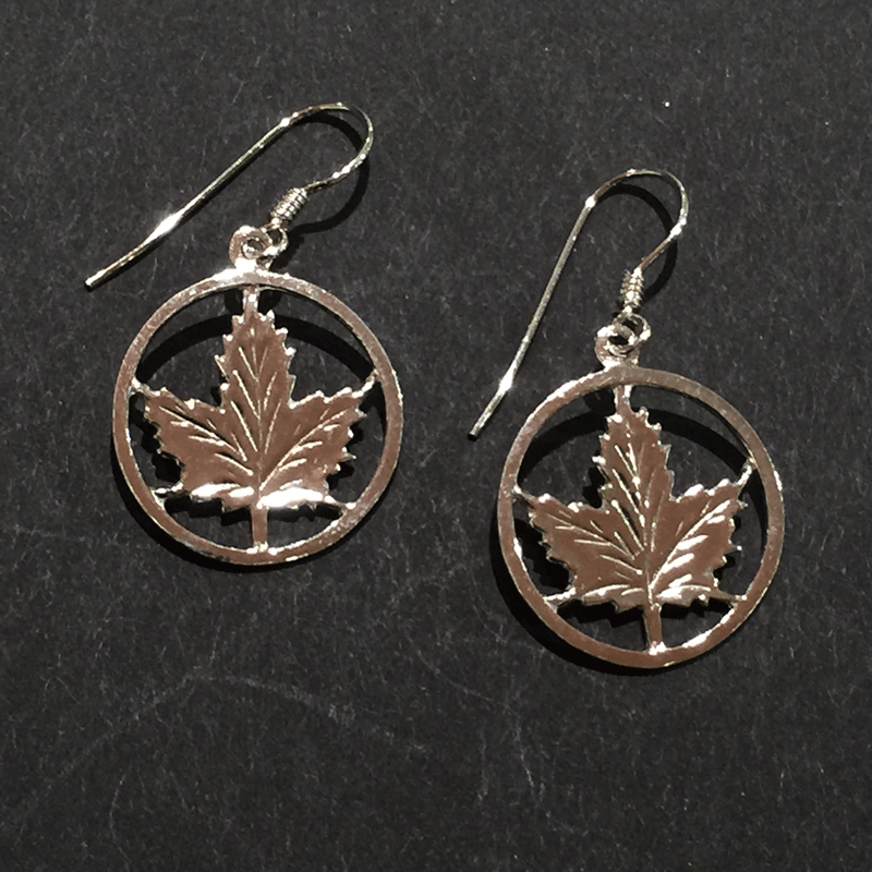 Two small sterling silver maple leaf earrings sit on a black background.  The maple leaves are enclosed by a silver circle. The earring hooks attach to the top of the circle.