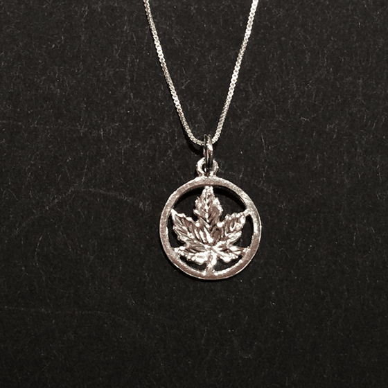 A small sterling silver maple leaf on a silver chain sits on a black background. The maple leaf is enclosed by a silver circle. The chain attaches to the top of the circle.