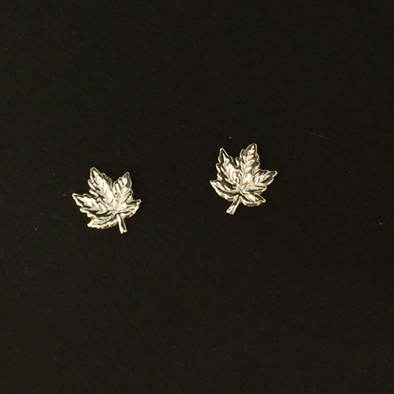 Two small sterling silver maple leaf earrings sit on a black background.  The earring backs cannot be seen.