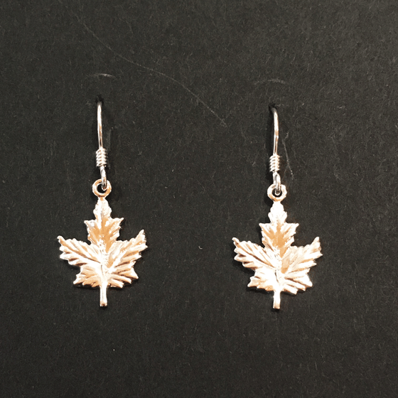 Two small sterling silver maple leaf earrings sit on a black background.  The earrings have silver earring hooks attached to the top point of the leaf charm.
