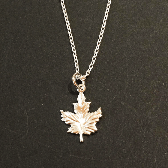A small sterling silver maple leaf on a silver chain sits on a black background. The maple leaf charm is attached to the chain at its top point.