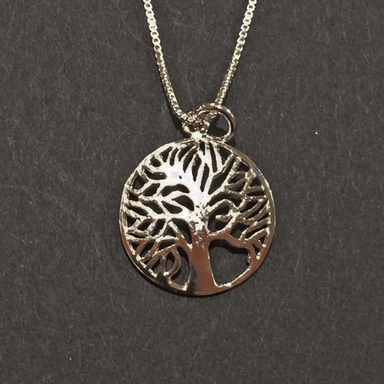 A sterling silver tree charm hangs from a silver chain on a black background. The tree is contained within a hoop. The tree's numerous thin branches radiate outward and fuse with the outer hoop.