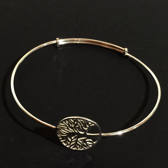 A sterling silver tree charm attached to a thin silver bracelet. The tree is contained within a hoop. The tree's numerous thin branches radiate outward and fuse with the outer hoop. The charm is attached to the bracelet along the back of the tree trunk. The bracelet may expand to fit a larger wrist, if necessary.