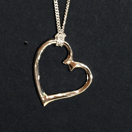 A sterling silver heart charm hangs from a silver chain on a black background. The chain attaches to the top left of the heart. The heart is asymmetrical and appears to curl towards the right.