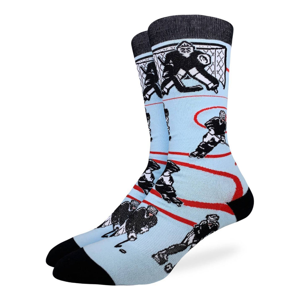 These fun socks feature a still image of a hockey game with a goalie and net at the top, while other players race around for the puck near the bottom. The background is an icey blue with red lines similar to that of an ice rink. The toe, heel, and rim of the sock are black. Spandex added to the 85% cotton blend gives the socks the perfect amount of stretch to hug your feet.