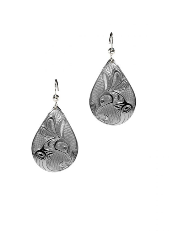 Silvery teardrop shaped earrings with a Haida design of a hummingbird drinking from a flower.