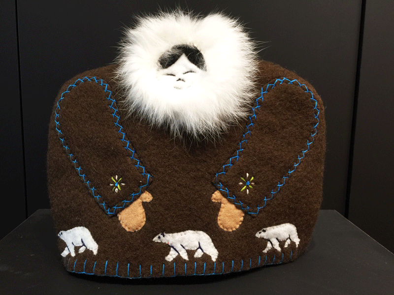 This tea cozy is in the shape of a smiling person wearing a brown parka with white fur around the face. The arms are stitched into the front with blue string. Small mitten covers hand poke out from the sleeves, and three polar bears are stitched onto the piece along the bottom.