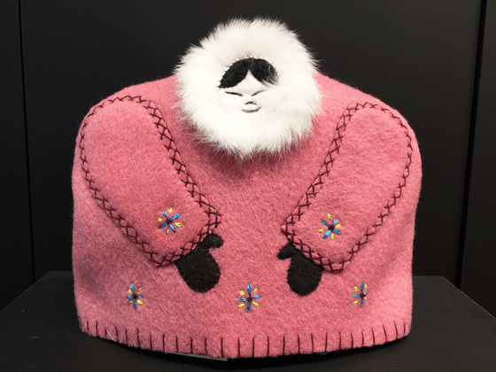 This tea cozy is in the shape of a smiling person wears a pink parka with white fur around their face. Darker pink stitching outlines the sleeves. Two brown mittens poke out from the sleeves, and blue and yellow stars are stitched along the bottom and on the sleeves.