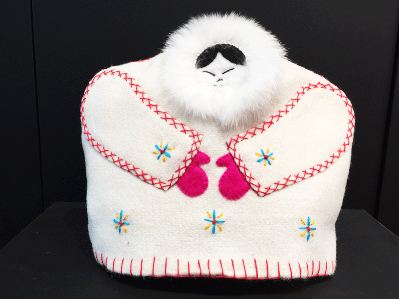 This tea cozy is in the shape of a smiling person wearing a white parka with white fur around their face. Red stitching outlines the sleeves, and pink mittens poke out from the end of them. blue and yellow stars are stitched onto the parka, three along the bottom, and one on each sleeve.
