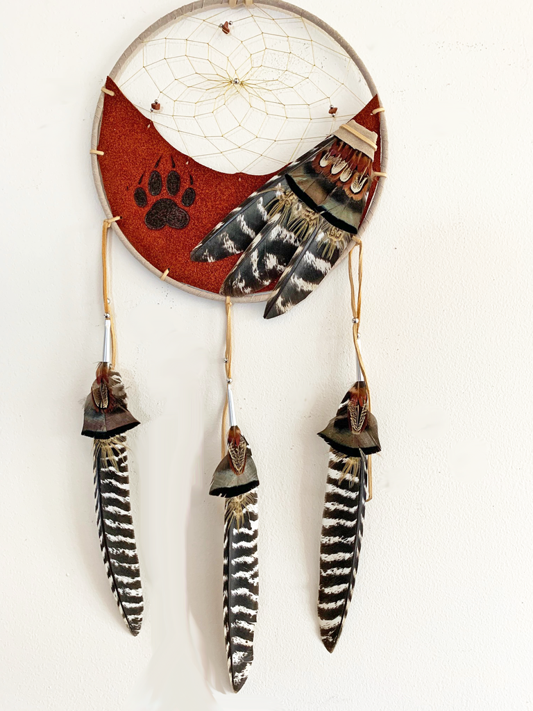 This dream catcher features a crescent of burnt orange leather with a wolf's paw print branded onto it. Above the leather, string is woven in a spiral pattern with small rocks and beads threaded into it. Brown, and white and black feathers lay across the leather on the right, and hang from three leather strings along the bottom.