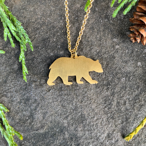 The silhouette of a bear walking left to right hangs from a gold chain. The chain attaches in the middle of the bear's back. The bear is gold plated with a matte finish.