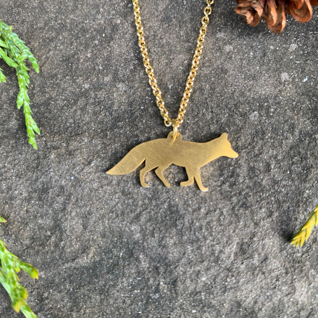The silhouette of a fox walking left to right hangs from a golden chain. The chain attaches in the middle of the fox's back. The fox is gold plated with a matte finish.