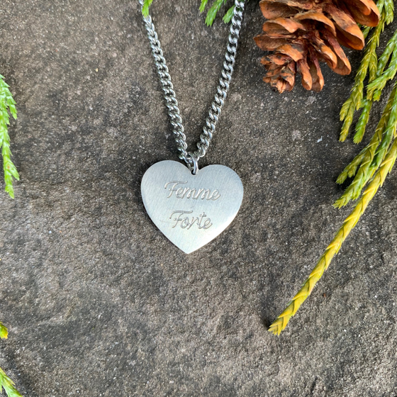 "A metal heart shaped charm hangs from a silver chain. The words ""Femme Forte"" are engraved in cursive on the charm. The charm is stainless steel with a matte finish."