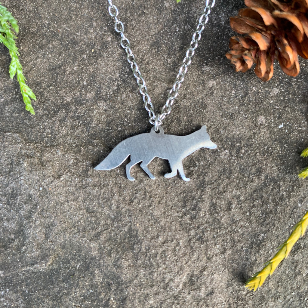 The silhouette of a fox walking left to right hangs from a silver chain. The chain attaches in the middle of the fox's back. The fox is stainless steel  with a matte finish.