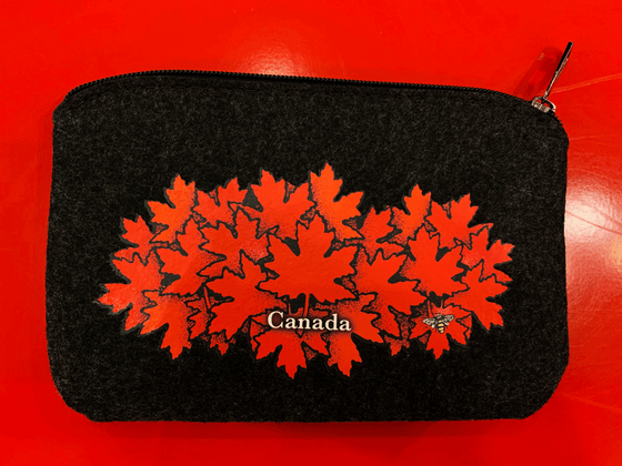 "This small dark grey pouch has an overhead zipper and features an art print of a spray of red maple leaves. At the bottom of the leaf pile the word ""Canada"" has been written in white text. At the bottom right of the picture is the artist's mark—a small picture of a bee."