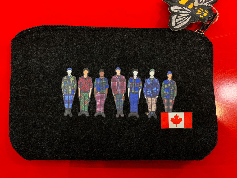 This small dark grey pouch has an overhead zipper and features an art print of seven soldiers standing at attention. Each soldier is wearing long pants and a jacket with a unique colourful tartan print. Someone has applied a small canada flag sticker to this pouch. The actual product does not have this sticker.