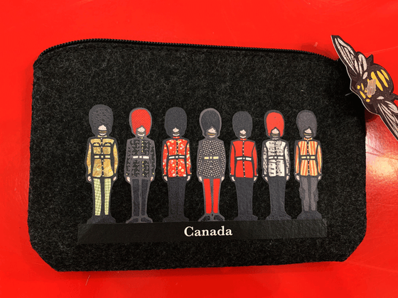 This small dark grey pouch has an overhead zipper and features an art print of seven soldiers standing at attention. They are al wearing long pants, belted jackets, and tall beefeater hats. Their jackets each have a unique colourful patterned print on them. At the bottom of the picture the word Canada is written in white text.