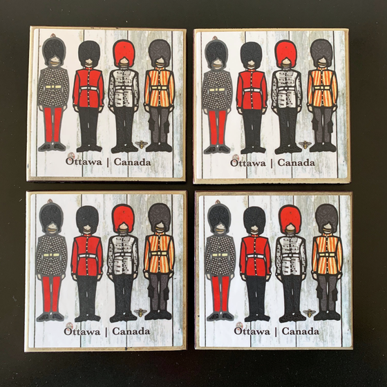 "This set of four ceramic coasters features an art print of four soldiers in ceremonial outfits. Each soldier wears long pants, a belted jacket, and a tall beefeater hat. Each jacket has a different pattern on it—one is plain, one has polka dots, one has stripes, and one has sheet music. At the bottom of the coaster the words ""Ottawa Canada"" have been written in black text."