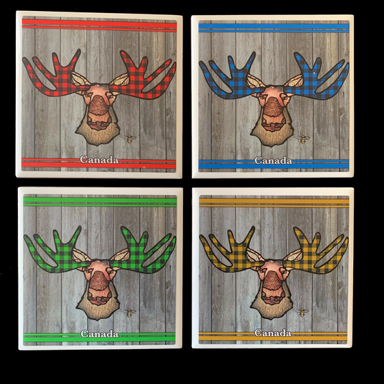 This set of four ceramic coasters features an art print of a moose. The moose's ear, nose, face and neck are all coloured with different shades of brown. The moose's antlers are patterned with buffalo check. A different colour buffalo check is used on each coaster. One is red, one blue, one yellow, and one green. Underneath the moose the word Canada has been written in white text. At the bottom right of the picture is the artists mark—a small picture of a bee.