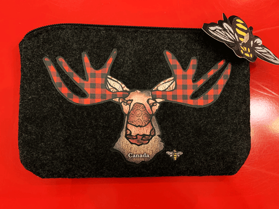 This small dark grey pouch has an overhead zipper and features an art print of a moose. The moose's antlers are coloured with red buffalo check. Its ears, nose, face and neck are all coloured with different shades of brown. At the bottom of the picture the word Canada is written in white text. At the bottom right is the artist's mark—a small picture of a bee.