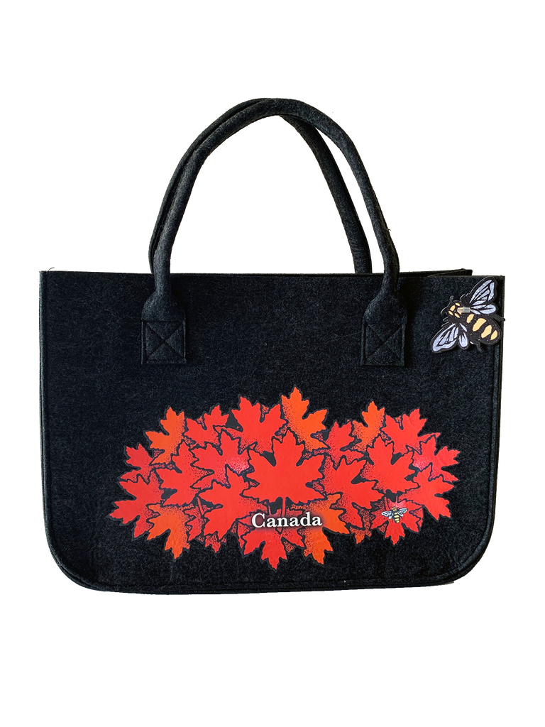 "This large dark grey felt bag has two overhead handles and features an art print of a spray of red maple leaves. At the bottom of the leaf pile the word ""Canada"" has been written in white text. At the bottom right of the picture is the artists mark—a small picture of a bee."