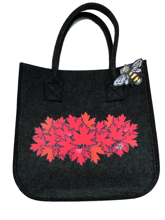 This small dark grey felt bag has two overhead handles and features an art print of a spray of red maple leaves. At the bottom right of the picture is the artists mark—a small picture of a bee.