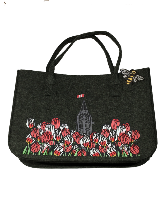 This large dark grey felt bag has two overhead handles and features an art print of the peace tower and a field of tulips. The peace tower is in the center of the picture and is flying the Canadian flag. The dense field of flowers has red tulips and Canada 150 tulips, which are white with fiery streaks of red. The line work gives the tulips an impression of stained glass.
