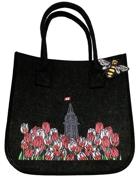 This small dark grey felt bag has two overhead handles and features an art print of the peace tower and a field of tulips. The peace tower is in the center of the picture and is flying the Canadian flag. The dense field of flowers has red tulips and Canada 150 tulips, which are white with fiery streaks of red. At the bottom right of the picture is the artists mark—a small picture of a bee.