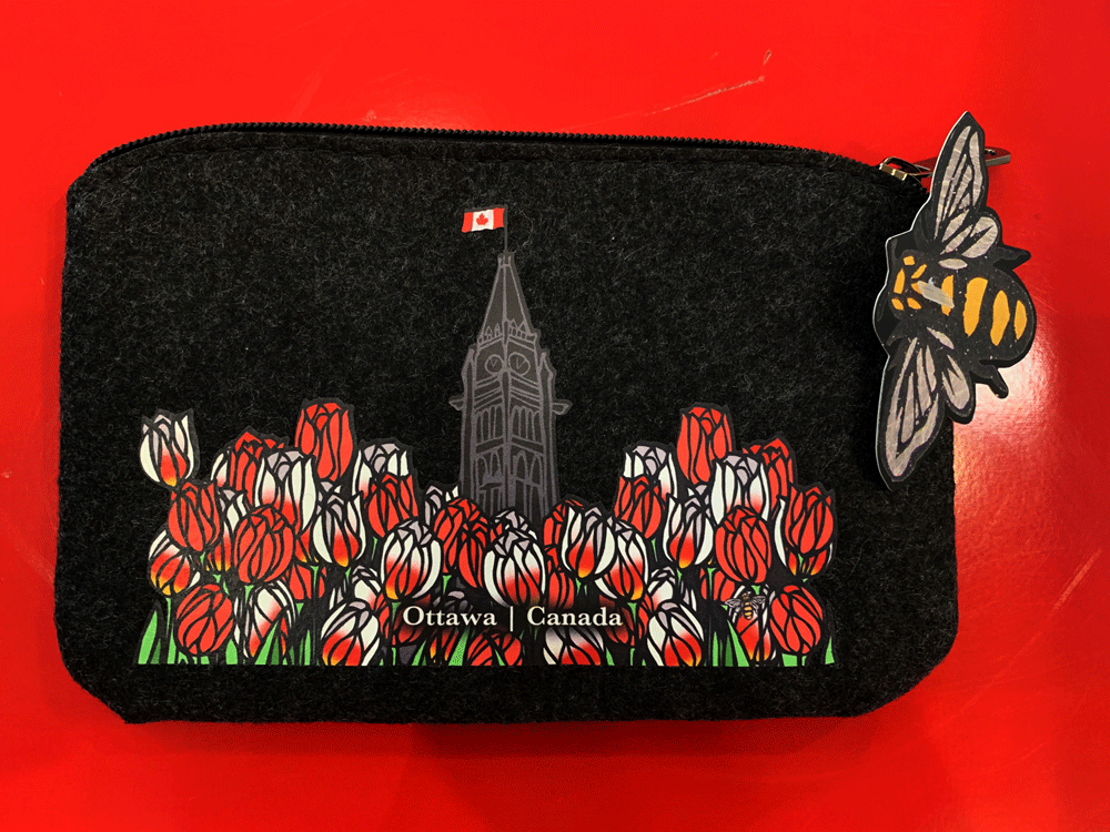 "This small dark grey pouch has an overhead zipper and features an art print of the peace tower and a field of tulips. The peace tower is in the center of the picture and is flying the Canadian flag. The dense field of flowers has red tulips and Canada 150 tulips, which are white with fiery streaks of red. At the bottom of the field the words ""Ottawa Canada"" are written in white text. At the bottom right of the picture is the artists mark—a small picture of a bee."