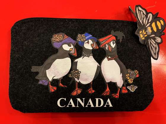 This small dark grey pouch has an overhead zipper and features an art print of three puffins. All three puffins wear a colourful hat with flowers or feathers in the brim. The left puffin carries a purse. The center and right puffins carry flowers and are wearing necklaces. The word Canada is written at the bottom of the picture in white text. At the bottom right of the picture is the artists mark—a small picture of a bee.