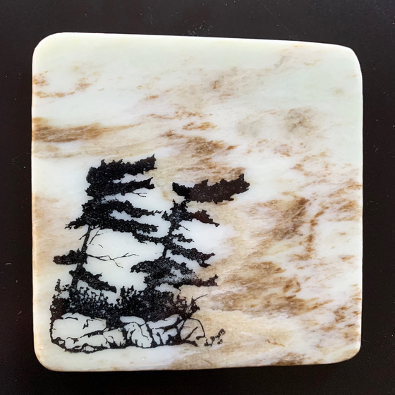 This coaster features the image of two pine trees on a rocky ledge with grass growing underneath. The image is on a piece of canadian shield marble with mineral lines running through in unique colours, lines, and patterns. The coaster is finished with a clear coat, giving it a shiny finish.