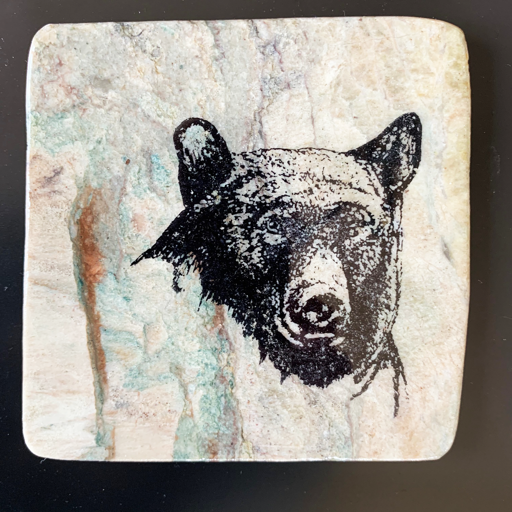 This coaster features the close up image of a black bear facing forward. The image is on a piece of canadian shield marble with mineral lines running through in unique colours, lines, and patterns. The coaster is finished with a clear coat, giving it a shiny finish.