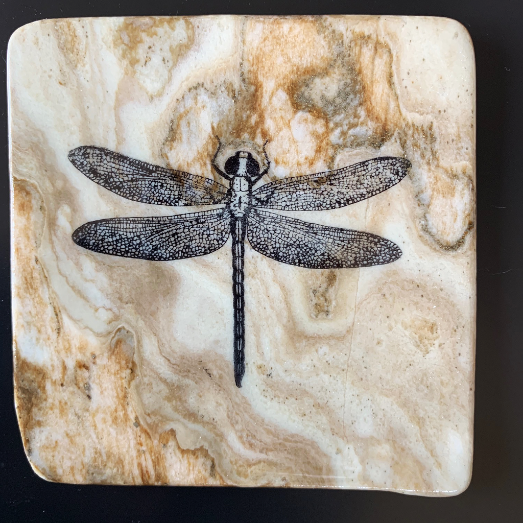 This coaster features the top down image of a dragonfly as rest. The image is on a piece of canadian shield marble with mineral lines running through in unique colours, lines, and patterns. The coaster is finished with a clear coat, giving it a shiny finish.