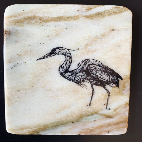 This coaster features the image of the side view of a heron as it walks through water. The image is on a piece of canadian shield marble with mineral lines running through in unique colours, lines, and patterns. The coaster is finished with a clear coat, giving it a shiny finish.