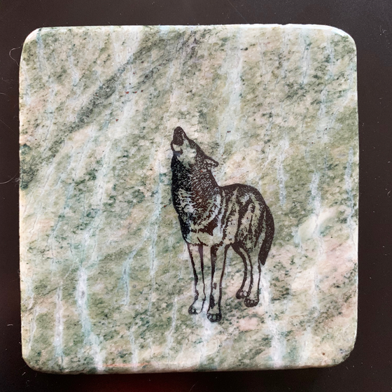 This coaster features the image of a wolf standing while howling into the sky. The image is on a piece of canadian shield marble with mineral lines running through in unique colours, lines, and patterns. The coaster is finished with a clear coat, giving it a shiny finish.