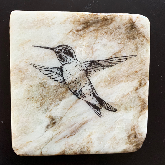 This coaster features the image of a hummingbird with its wings out in mid-flight. The image is on a piece of canadian shield marble with mineral lines running through in unique colours, lines, and patterns. The coaster is finished with a clear coat, giving it a shiny finish.