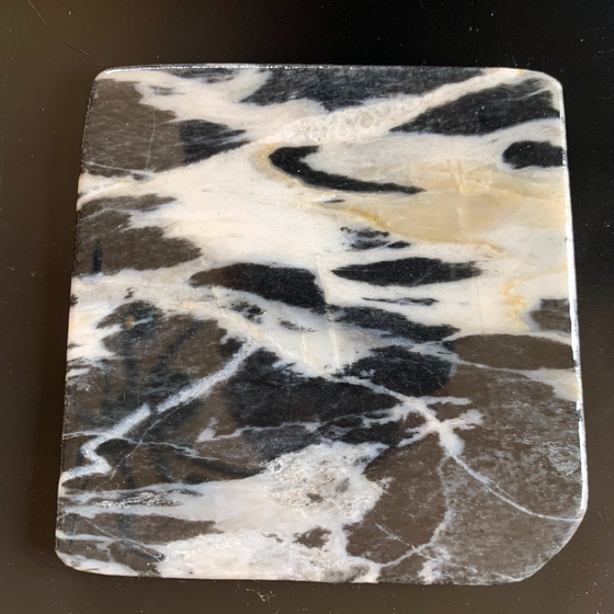 This coaster is made of a piece of canadian shield marble with mineral lines running through in unique colours, lines, and patterns. The coaster is finished with a clear coat, giving it a shiny finish.