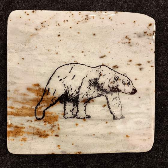 This coaster features the image of the side view of a polar bear as it walks. The image is on a piece of canadian shield marble with mineral lines running through in unique colours, lines, and patterns. The coaster is finished with a clear coat, giving it a shiny finish.