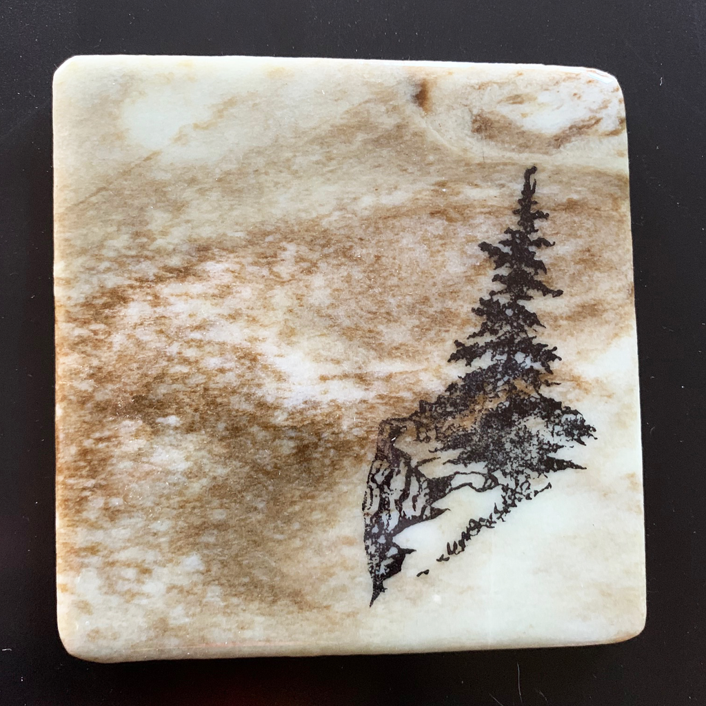 This coaster features the image of a pine tree on the edge of a rocky ledge with grass growing around it. The image is on a piece of canadian shield marble with mineral lines running through in unique colours, lines, and patterns. The coaster is finished with a clear coat, giving it a shiny finish.