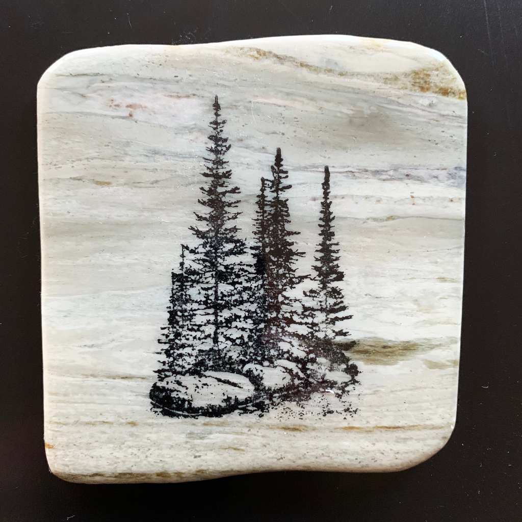 This coaster features the image of a small group of trees on a rocky ledge with grass growing around them. The image is on a piece of canadian shield marble with mineral lines running through in unique colours, lines, and patterns. The coaster is finished with a clear coat, giving it a shiny finish.